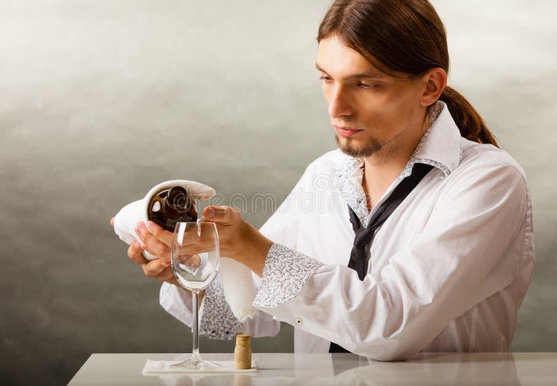 Equipe o vinho de derramamento do garçom no vidro fotografia de stock