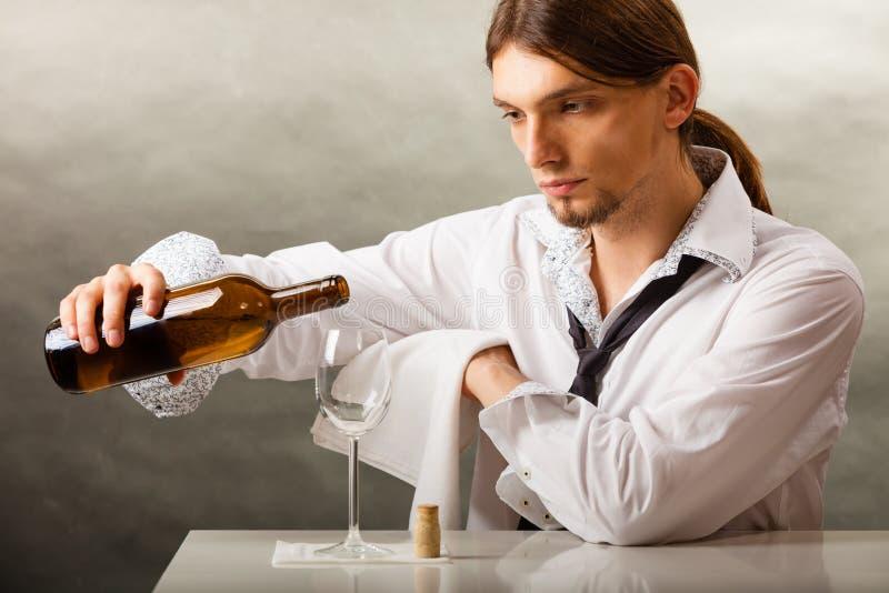 Equipe o vinho de derramamento do garçom no vidro fotografia de stock royalty free