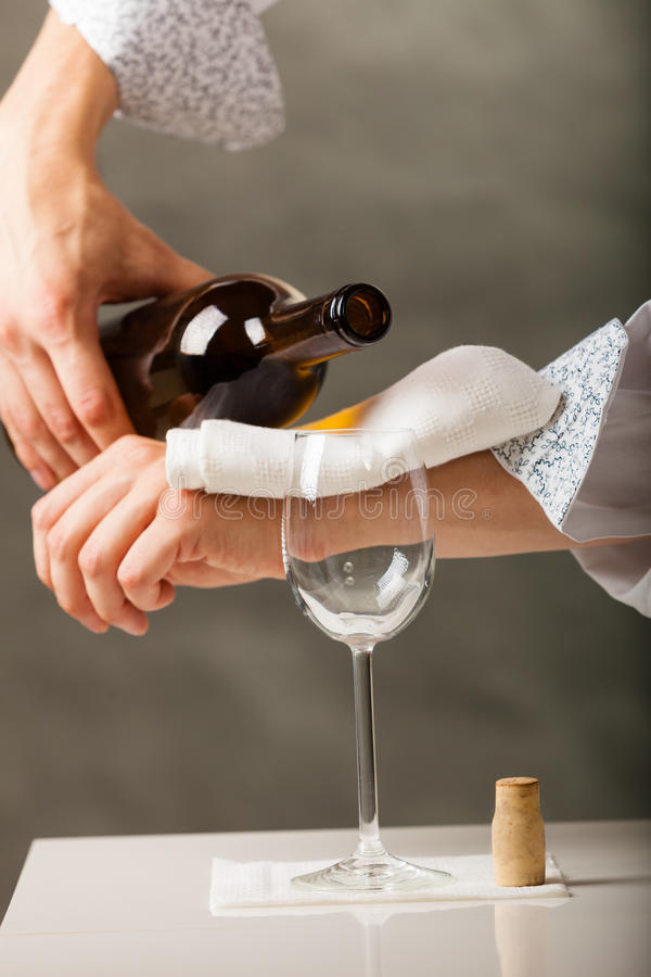 Equipe o vinho de derramamento do garçom no vidro imagem de stock