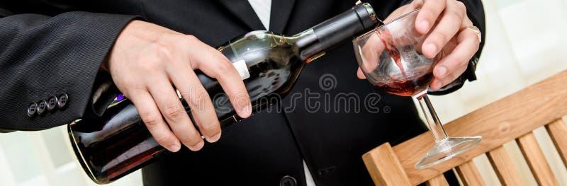 Equipe o vinho vermelho de derramamento do frasco em um vidro imagem de stock royalty free