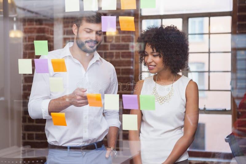 Equipe ocasional do negócio que olha notas pegajosas imagens de stock