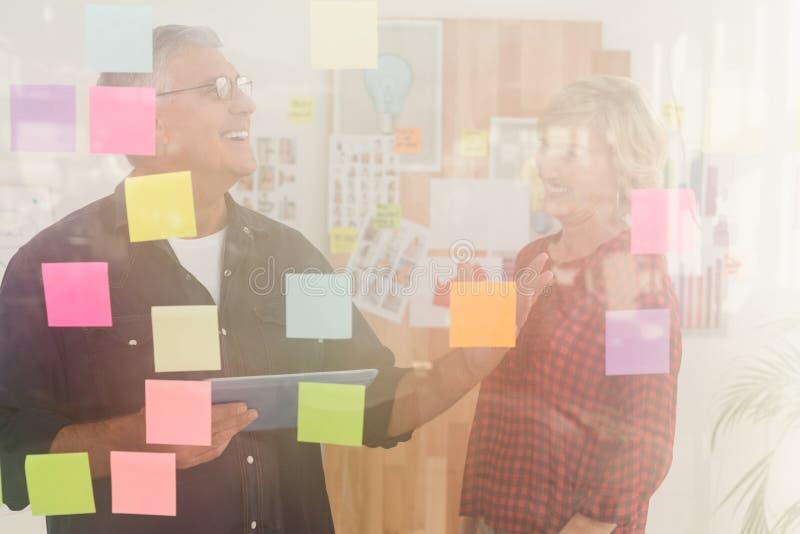 Equipe ocasional do negócio que ri sobre uma tabuleta fotografia de stock royalty free