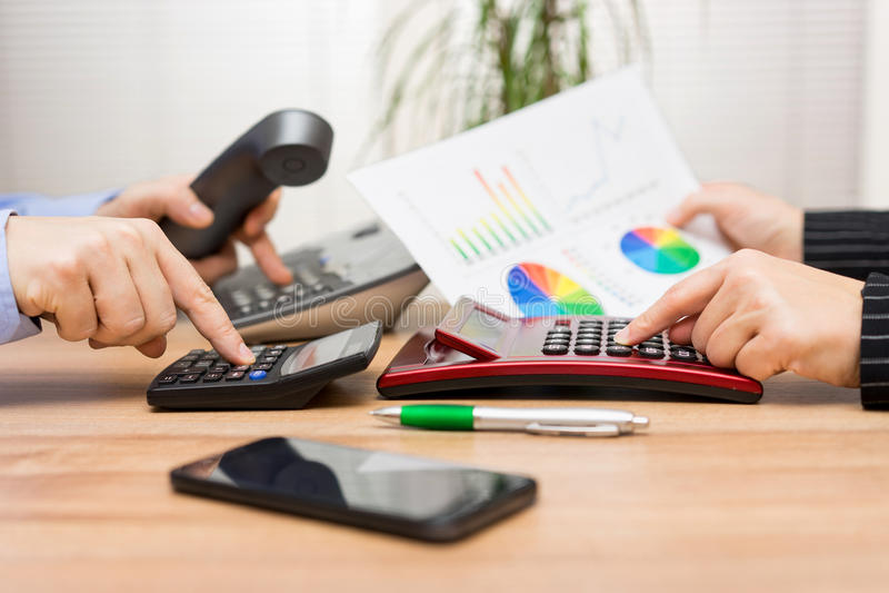 A equipe ocupada do negócio está trabalhando no relatório financeiro e está chamando c foto de stock