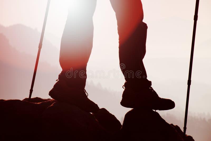 Equipe os pés do caminhante e os polos estão na rocha do pico de montanha Homem nas montanhas foto de stock