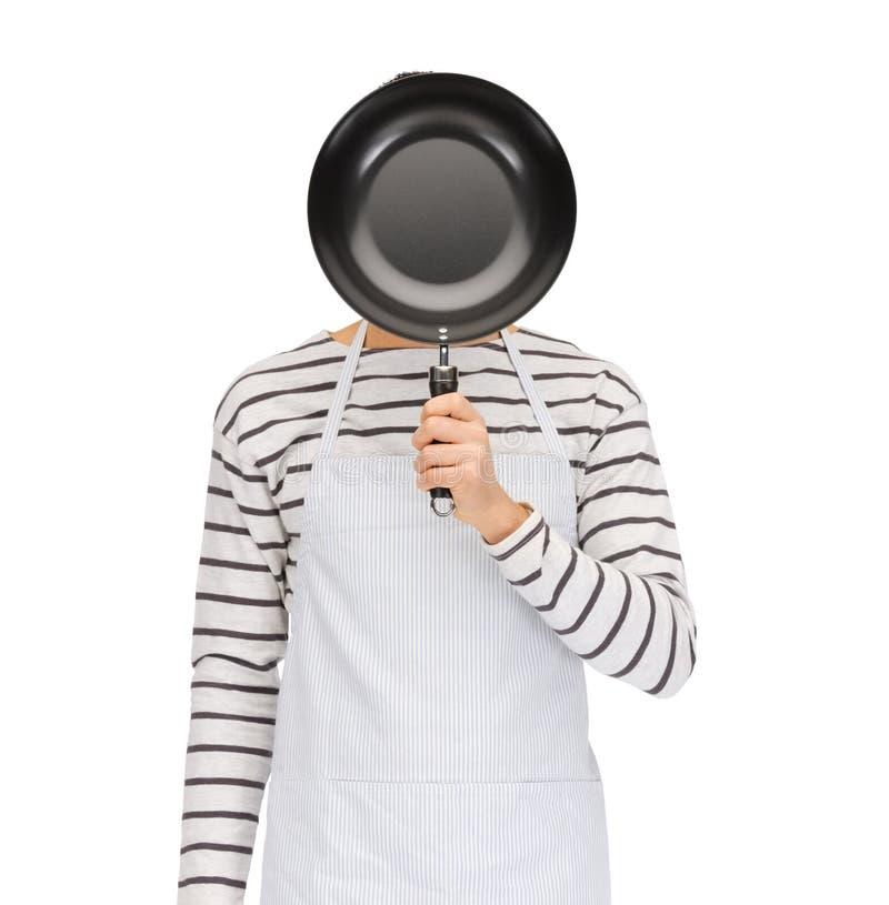 Equipe ou cozinhe na cara escondendo do avental atrás da frigideira imagens de stock royalty free