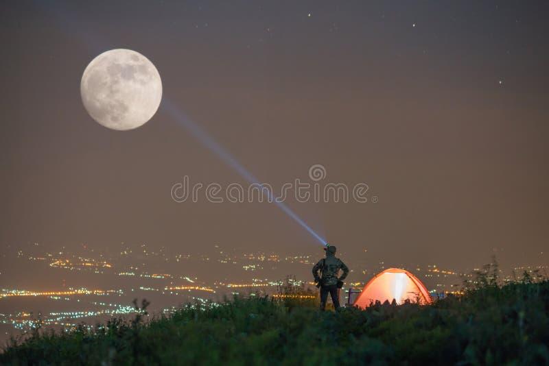 Equipe a posição com flash e a barraca de acampamento alaranjada iluminada imagem de stock royalty free
