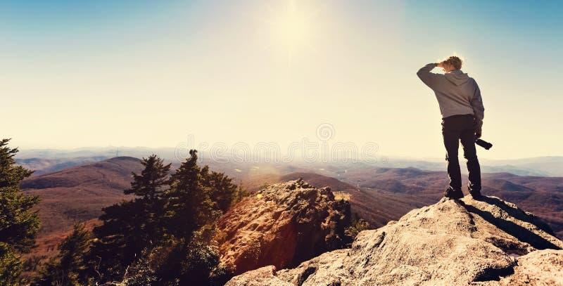 Equipe a posição em uma borda dos penhascos que negligencia as montanhas abaixo fotografia de stock
