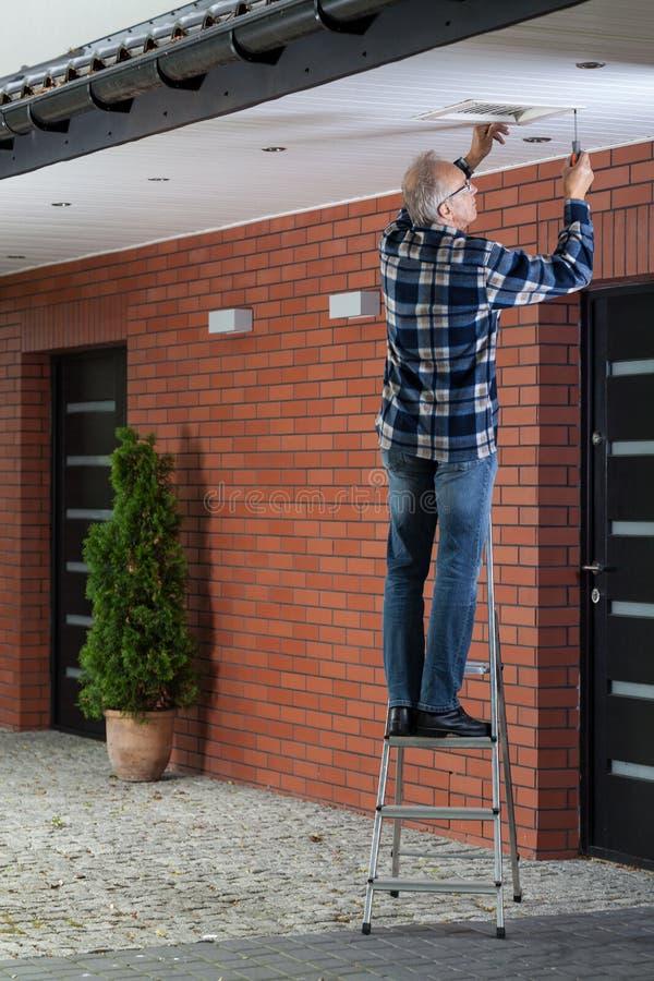 Equipe a posição na escada e o aperto da grade da ventilação imagem de stock royalty free