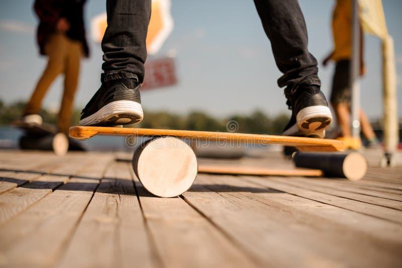Equipe a posição na placa do equilíbrio no cais de madeira fotografia de stock