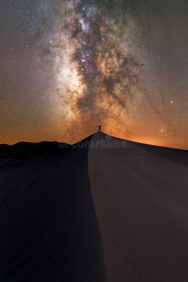 Equipe a posição sob as estrelas em uma duna de areia foto de stock royalty free