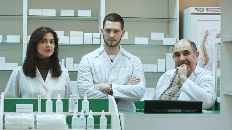 Equipe positiva dos farmacêuticos que olham a câmera na farmácia do hospital imagem de stock
