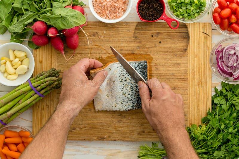 Equipe a preparação de uma faixa salmon fresca para cozinhar imagens de stock royalty free