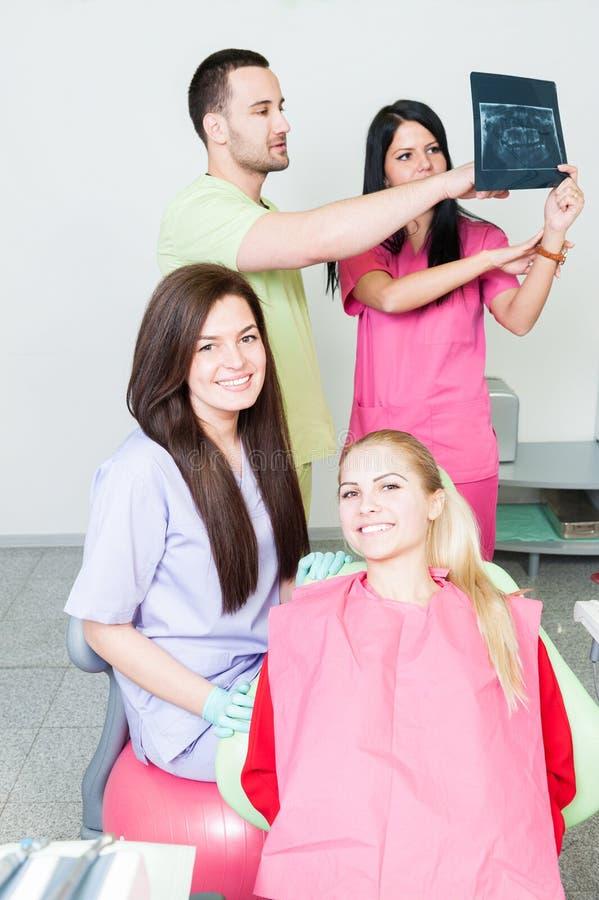 Equipe profissional do dentista que analisa um raio X fotografia de stock royalty free