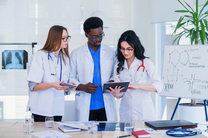 Equipe profissional dos médicos multirraciais que têm uma conferência Multi grupo étnico de estudantes de Medicina Cuidados m?dic imagem de stock royalty free