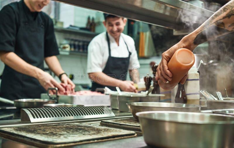Equipe profissional -- Molde B do negócio corporativo Cozinheiros novos alegres que preparam o alimento junto em uma cozinha do r imagem de stock