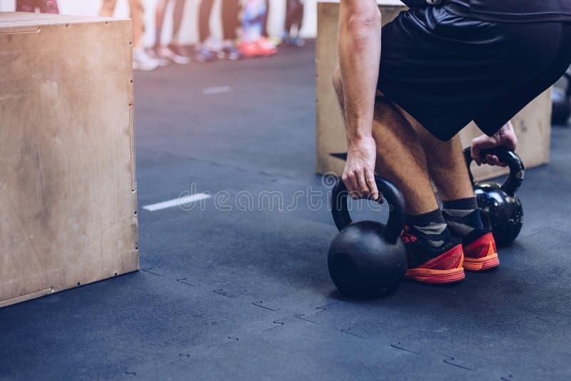 Equipe puxar pesos dos kettlebells no gym funcional da aptidão fotografia de stock