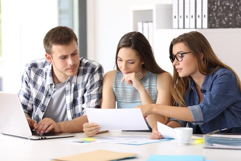 Equipe que coworking analisando o relatório no escritório imagem de stock