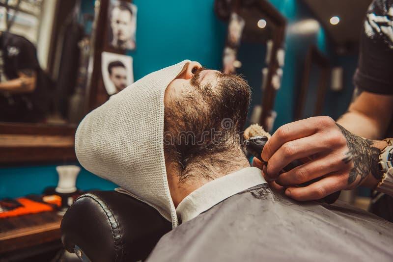 Equipe a rapagem de sua barba no cabeleireiro profissional fotografia de stock