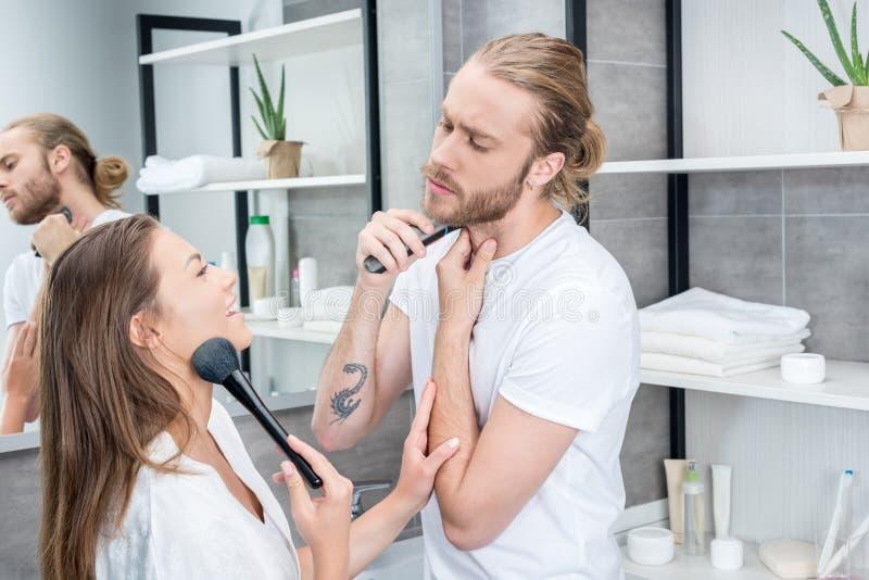 Equipe a rapagem de sua barba quando mulher que aplica o pó de cara no banheiro fotografia de stock