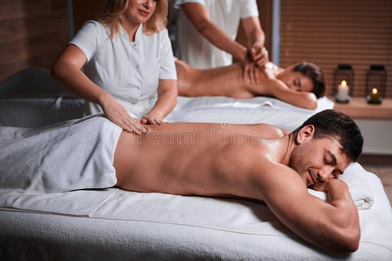 Equipe a recepção da massagem traseira do massagista nos termas imagens de stock royalty free