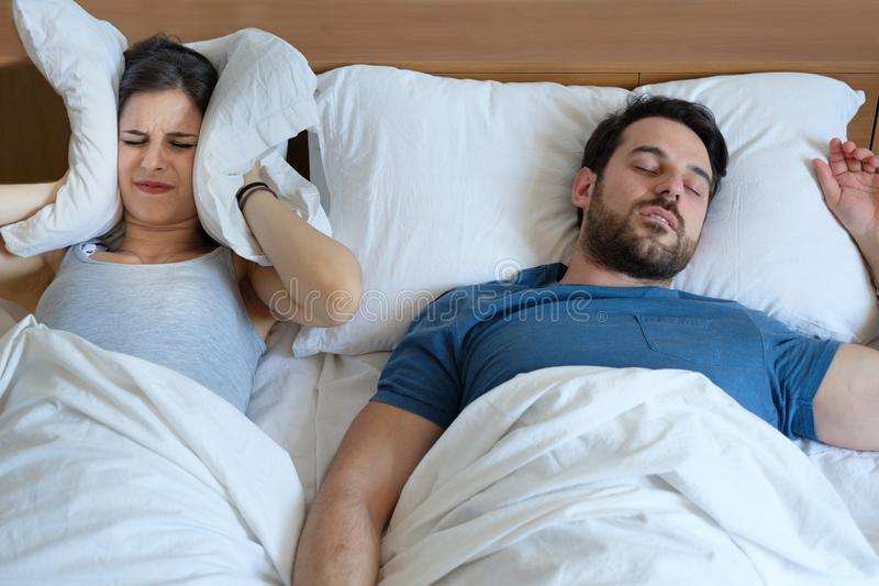 Equipe ressonar na cama devido à desordem de sono da apneia da noite imagem de stock