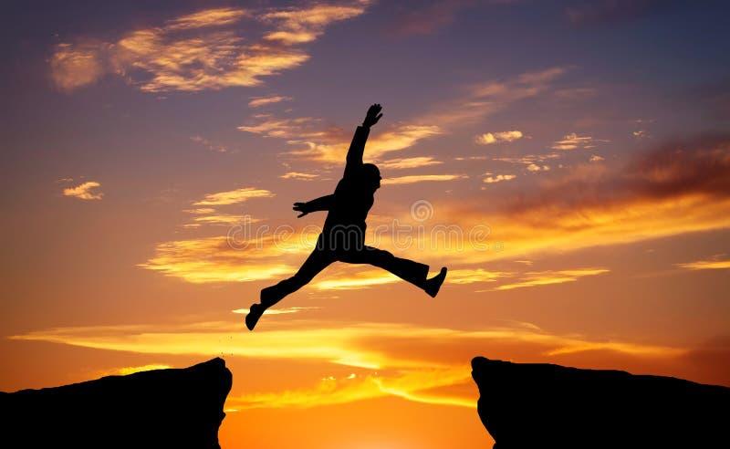 Equipe saltam com a diferença no fundo impetuoso do por do sol foto de stock royalty free