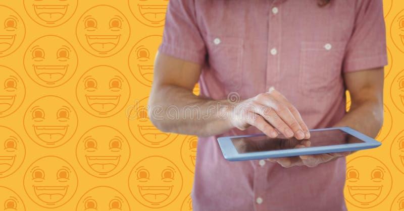 Equipe a seção meados de da camisa cor-de-rosa com a tabuleta contra o teste padrão amarelo do emoji foto de stock royalty free