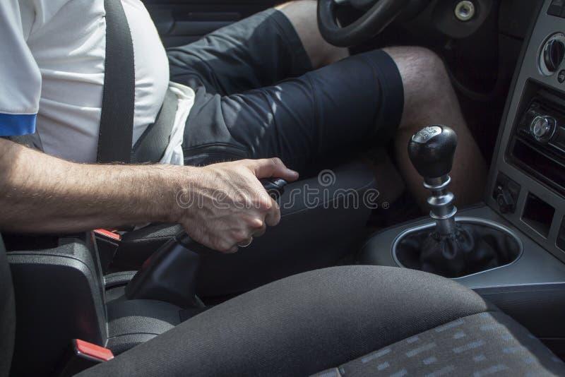 Equipe senta-se atrás da roda de um automóvel de passageiros e puxa-se o handbrake fotografia de stock