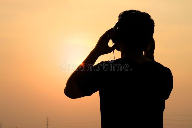 Equipe a silhueta que escuta os fones de ouvido no por do sol imagens de stock royalty free