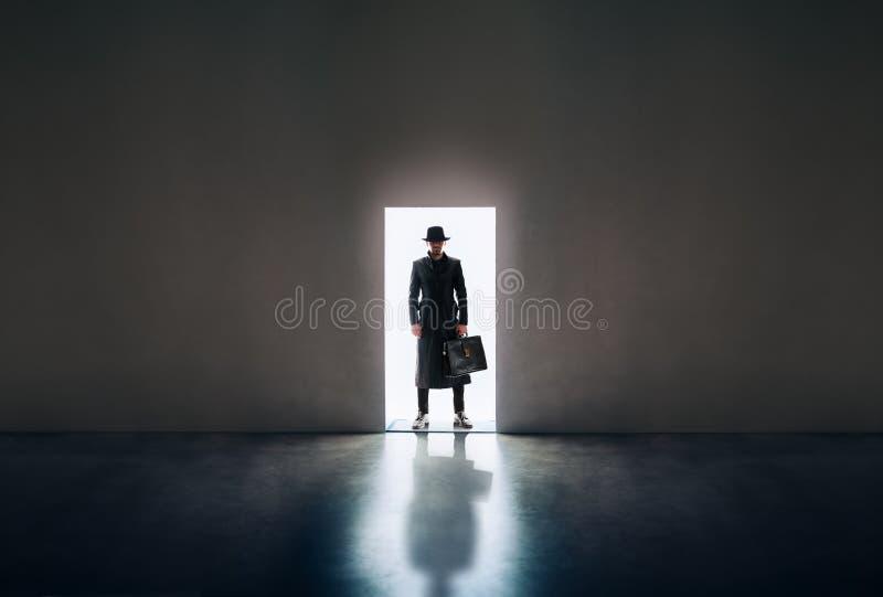 Equipe a silhueta que está à vista da porta de abertura no roo escuro imagens de stock