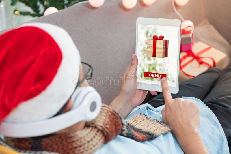 Equipe a tabuleta do uso que envia chirstms e presente do ano novo ao onli do amigo fotos de stock royalty free