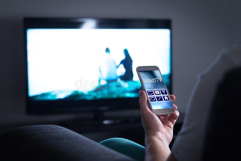 Equipe a televisão de observação e a utilização do controlo a distância esperto app da tevê imagem de stock