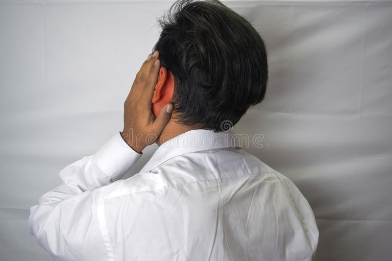 Equipe ter a dor de orelha que toca em sua orelha inflamada dolorosa isolada no fundo branco foto de stock royalty free