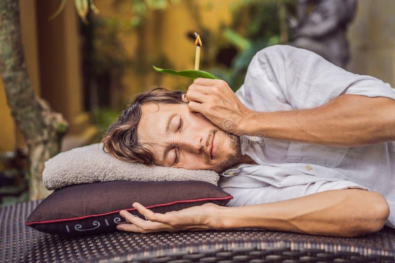 Equipe ter uma terapia da vela da orelha contra o contexto de um jardim tropical imagem de stock royalty free