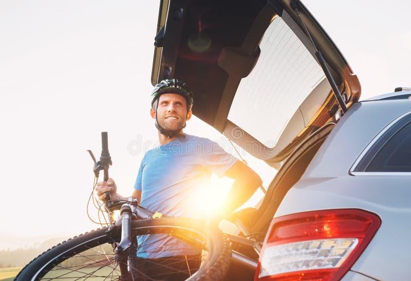Equipe a tomada de sua bicicleta para fora do tronco de um carro imagem de stock