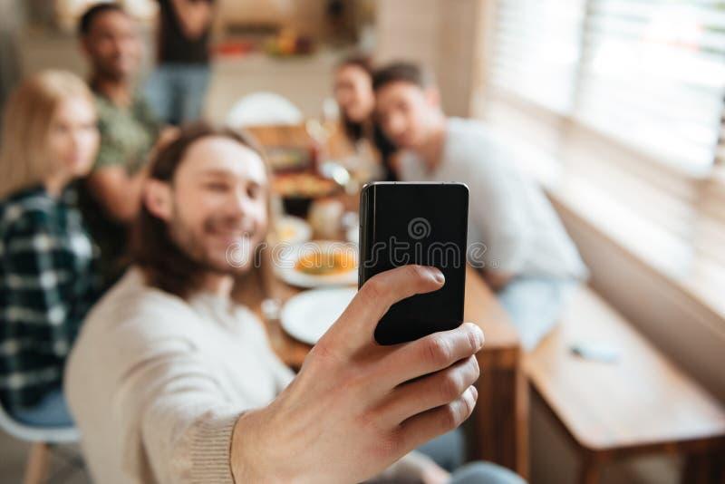 Equipe a tomada de uma foto do selfie com os amigos na cozinha fotografia de stock royalty free