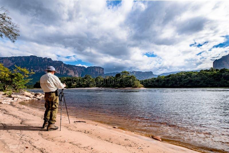 Equipe a tomada de uma fotografia em Canaima, Venezuela imagem de stock