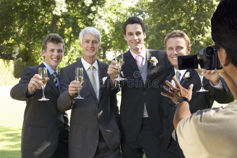 Equipe a tomada de uma imagem de cinco homens que brindam com vidros de vinho no banquete de casamento foto de stock royalty free