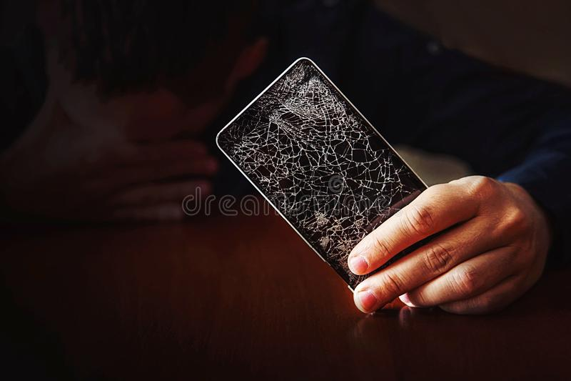 Equipe triste, ao ver o telefone no fundo escuro imagens de stock royalty free