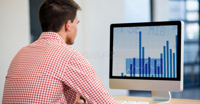 Equipe usando o computador de secretária que indica uma carta do gráfico na tela foto de stock
