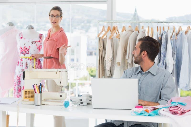 Equipe usando o portátil com o desenhador de moda que trabalha no estúdio imagens de stock royalty free