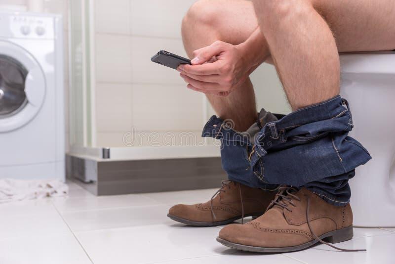 Equipe usando o telefone ao sentar-se em uma bacia de toalete imagem de stock royalty free