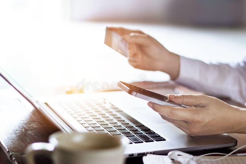 Equipe usando pagamentos móveis com o cartão de crédito para a compra em linha no fundo do portátil fotos de stock