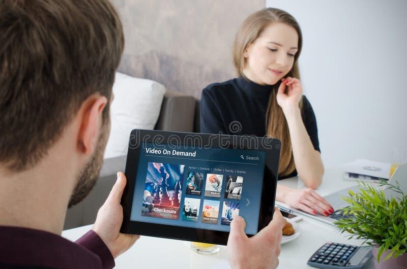 Equipe usando a tabuleta digital para o filme de observação no serviço de VOD imagem de stock royalty free