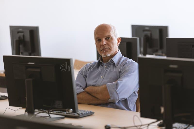 Equipe a vista da câmera com os braços dobrados ao sentar-se no desktop fotos de stock royalty free