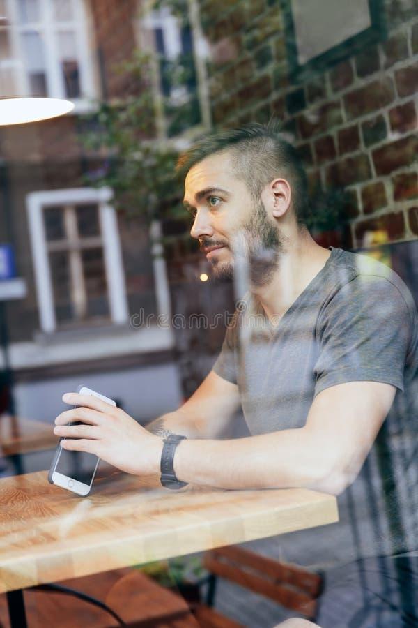 Equipe a vista de assento e de pensamento pela janela imagem de stock