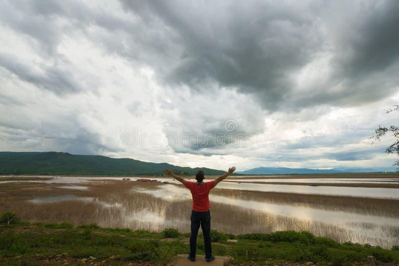 Equipe a vista do barco de casa de flutuação da opinião do lago da aldeia piscatória no por do sol com nuvem, chuva e tempestade imagem de stock