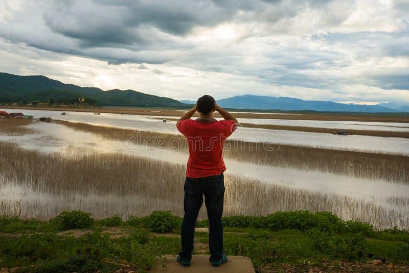 Equipe a vista do barco de casa de flutuação da opinião do lago da aldeia piscatória no por do sol com nuvem, chuva e tempestade fotografia de stock
