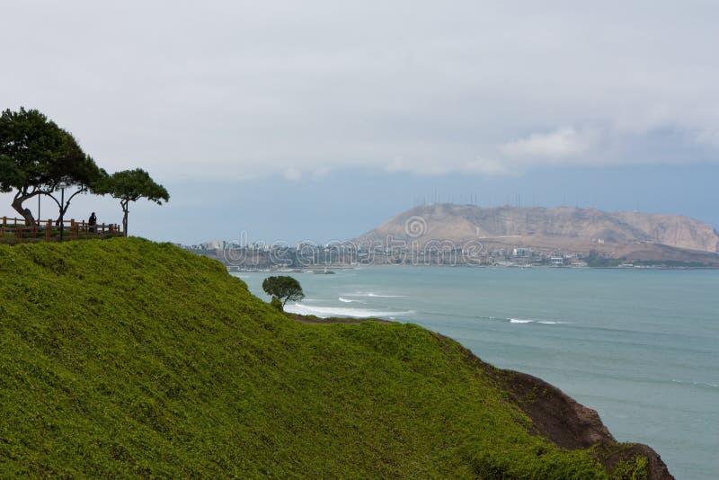 Equipe a vista sobre o oceano de um penhasco em Miraflores em Lima, P imagens de stock