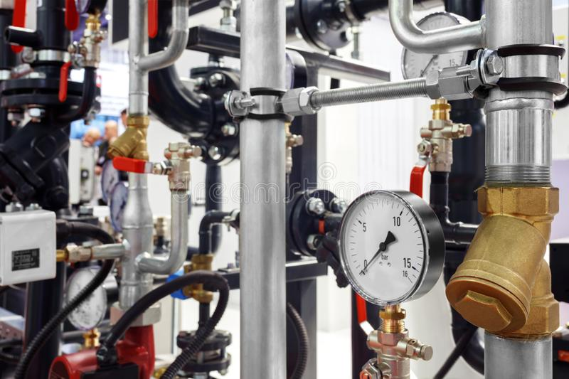 The equipment of the boiler-house, - valves, tubes, pressure gauges, thermometer. Close up of manometer, pipe, flow meter, water p. Umps and valves of heating stock photos